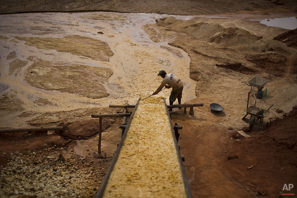 In this Nov. 14, 2015 photo, an artisanal diamond miner separates large rocks from smaller ones at an abandoned mine in Areinha, Minas Gerais state, Brazil. The mining process can take weeks. First miners excavate the soil. Once the layer of gravel is reached which can be as deep as 50 meters, they extract the rocks with the help of small pumps powered by old truck engines and begin the manual separation process to filter the small rocks, and if lucky, the diamonds. (AP Photo/Felipe Dana)