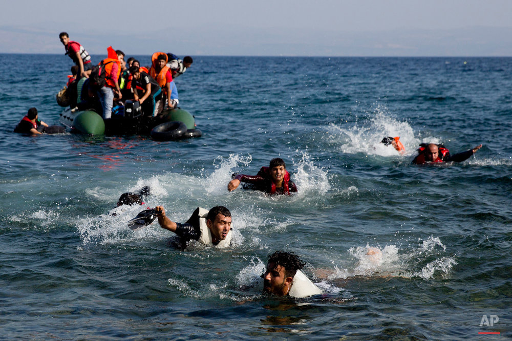 Migrant whose boat stalled at see while crossing from Turkey to Greece swim to approach a shore of the island of Lesbos, Greece, on Sunday, Sept. 20, 2015. A boat with 46 migrants or refugees has sunk Sunday in Greece and the coast guard says it is searching for 26 missing off the eastern Aegean island of Lesbos. (AP Photo/Petros Giannakouris)