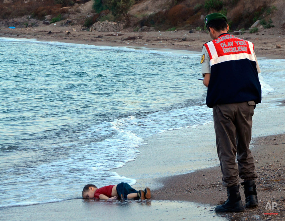 A paramilitary police officer investigates the scene before carrying the lifeless body of 3-year-old Aylan Kurdi from the sea shore, near the beach resort of Bodrum, Turkey, early Wednesday, Sept. 2, 2015. A number of migrants are known to have died and some are still reported missing, after boats carrying them to the Greek island of Kos capsized. (AP Photo/Nilufer Demir, DHA)