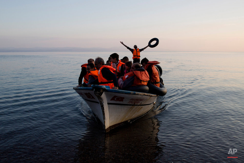 A Syrian refugee praises god as he arrive with others from Turkey on the shores of the Greek island of Lesbos, on a fishing boat, Sunday Sept. 27, 2015. More than 260,000 asylum-seekers have arrived in Greece so far this year, most reaching the country's eastern islands on flimsy rafts or boats from the nearby Turkish coast.(AP Photo/Petros Giannakouris)