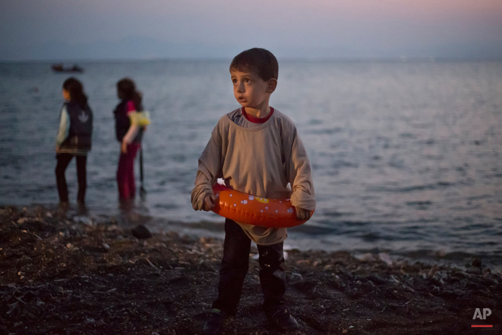 A Syrian migrant boy still wearing a swimming ring stands on the beach upon his arrival with other migrants by a dinghy at the southeastern Greek island of Kos, Greece, early Thursday, Aug. 20, 2015. (AP Photo/Alexander Zemlianichenko)