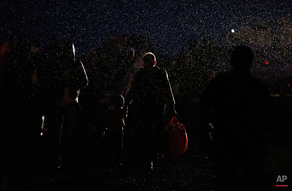 Migrants arrive during heavy rain at the Hungarian-Austrian border in Nickelsdorf,  Austria, Saturday, Sept. 5, 2015, where they came from Budapest as Austria in the early-morning hours said it and Germany would let them in.  (AP Photo/Frank Augstein)