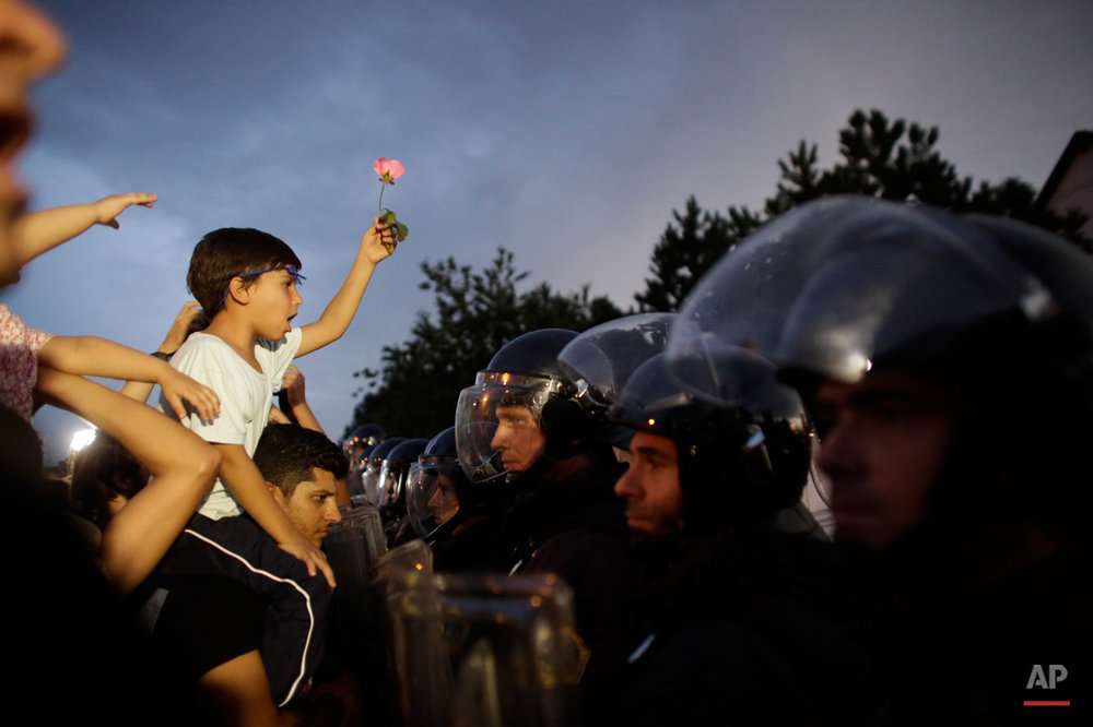 A boy with a flower sits on the shoulders of a man as a group of refugees and supporters face Slovenian police blocking the entrance to Slovenia at the border crossing in the Croatian village of Harmica, Friday, Sept. 18, 2015. (AP Photo/Markus Schreiber)