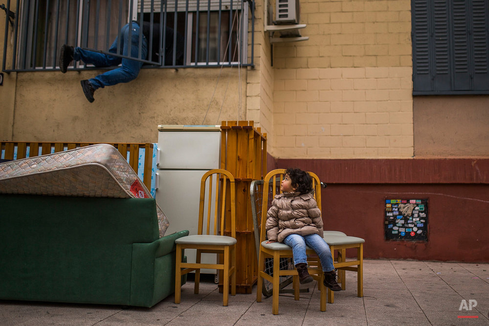 In this Wednesday, Feb. 11, 2015, photo, Diana Sofia Meliton, 2 years old, sits outside together with belongings after her and her family got evicted by the police and watches a housing right activist re-opening her apartment for them to live in Madrid, Spain. (AP Photo/Andres Kudacki)