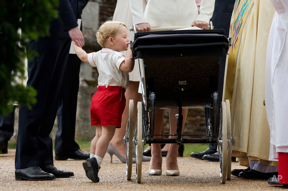 Britain's Prince George gets up on tip-toes to peek into the pram of his sister Princess Charlotte flanked by his parents Prince William and Kate the Duchess of Cambridge as they leave after Charlotte's Christening at St. Mary Magdalene Church in Sandringham, England, Sunday, July 5, 2015.  (AP Photo/Matt Dunham)