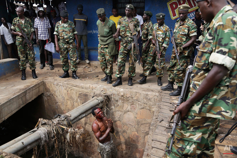 Jean Claude Niyonzima, a suspected member of the ruling party's Imbonerakure youth militia, pleads with soldiers to protect him from a mob of demonstrators after he came out of a sewer  in the Cibitoke  district of Bujumbura, Burundi, Thursday, May 7, 2015. (AP Photo/Jerome Delay)