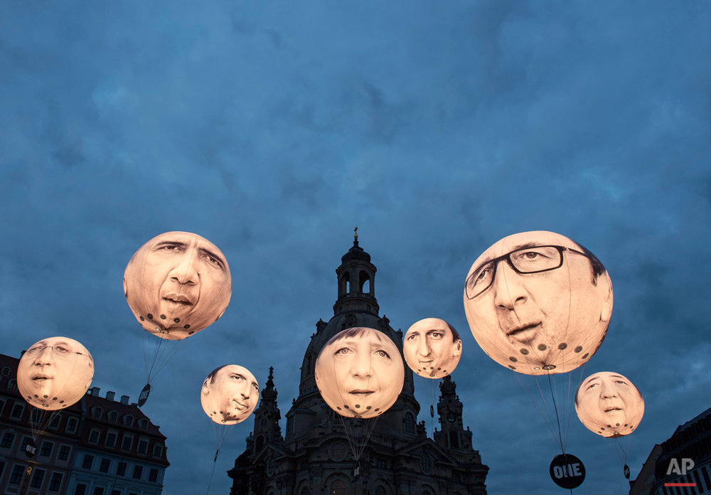 Activists of the international campaigning and advocacy organisation ONE install illuminated balloons with portraits of the G7 heads of state in front of the Frauenkirche cathedral (Church of Our Lady) prior the G7 Finance Ministers meeting in Dresden, eastern Germany, Wednesday, May 27, 2015.  (AP Photo/Jens Meyer)