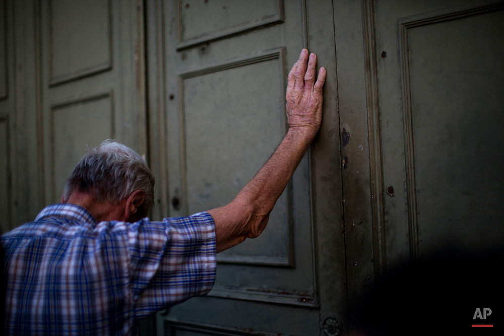 A pensioner leans against the main gate of the national bank of Greece as he waits to withdraw a maximum of 120 euros ($134) for the week in Athens in central Athens, Tuesday, July 7, 2015. (AP Photo/Emilio Morenatti)