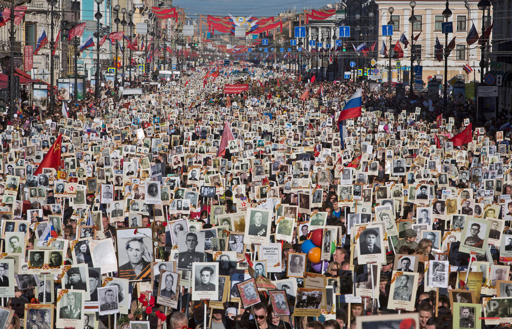 In this photo dated Saturday, May 9, 2015, local residents carry portraits of their ancestors, participants in World War Two as they celebrate the 70th anniversary of the defeat of the Nazis in World War II in St. Petersburg, Russia. About 100,000 people walked in central streets in a march named 'Immortal Regiment' while carrying portraits of their relatives who fought in World War Two. (AP Photo/Dmitry Lovetsky)