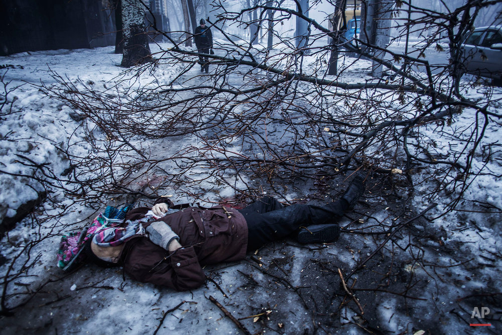 A person walk near the remains of a man lying near a bus stop that was damaged in shelling in Donetsk, eastern Ukraine, Tuesday, Jan. 20, 2015. At least three civilians were killed in shelling Tuesday in eastern Ukraine as fighting continued between government and rebel forces in the separatist-held city of Donetsk. (AP Photo/Manu Brabo)