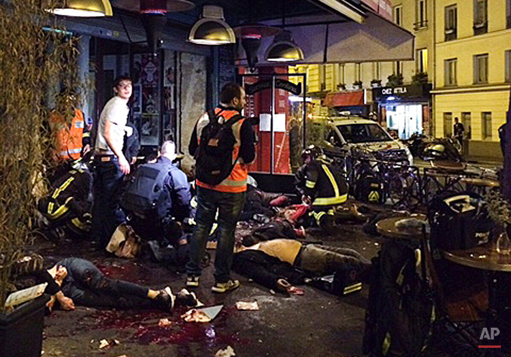 Victims of a shooting attack lie on the pavement outside La Belle Equipe restaurant in Paris Friday, Nov. 13, 2015.   (Anne Sophie Chaisemartin via AP)
