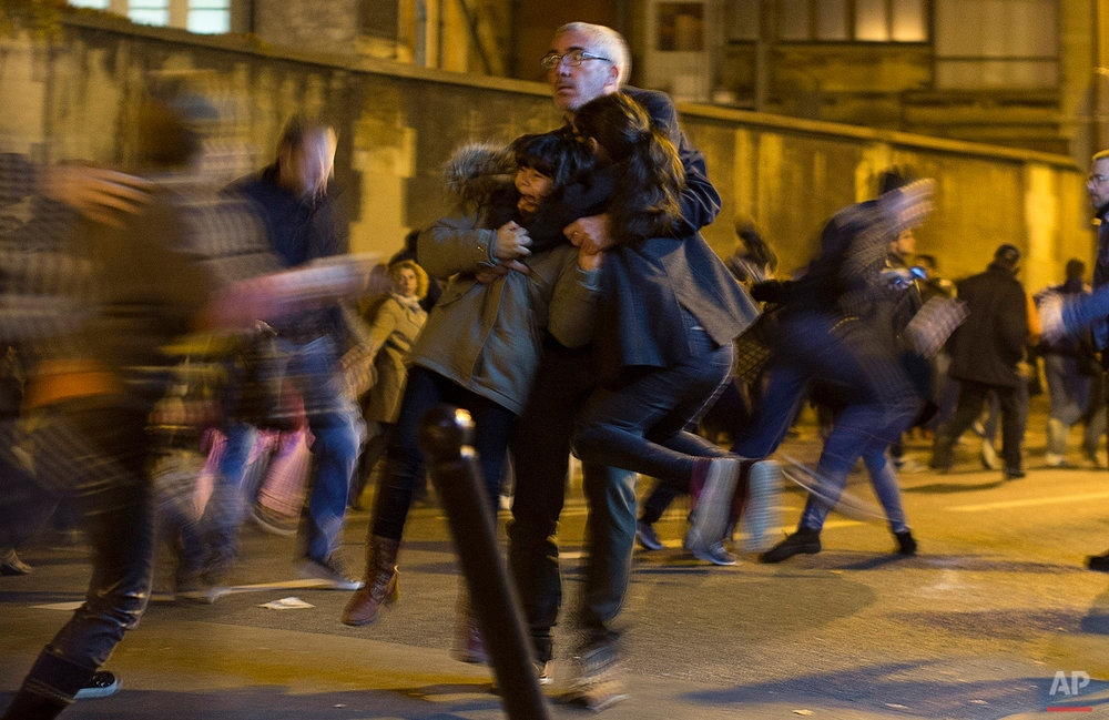 A man carries two children after panic broke out among mourners who payed their respect at the attack sites at restaurant Le Petit Cambodge (Little Cambodia) and the Carillon Hotel in Paris, Sunday, Nov. 15, 2015. (AP Photo/Peter Dejong)