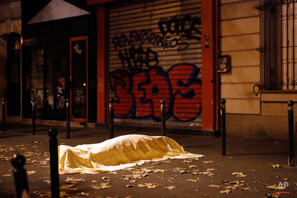 A victim of a terrorist attack lies dead outside the Bataclan theater in Paris, Nov. 13, 2015. The Islamic State group claimed responsibility for Friday's attacks on a stadium, a concert hall and Paris cafes that left more than 120 people dead and over 350 wounded.   (AP Photo/Jerome Delay)