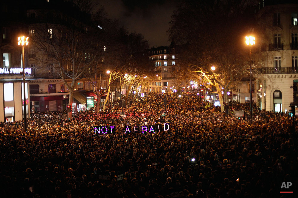 People gather to pay respect for the victims of a terror attack against satirical newspaper Charlie Hebdo, in Paris, Wednesday, Jan. 7, 2015. (AP Photo/Thibault Camus)