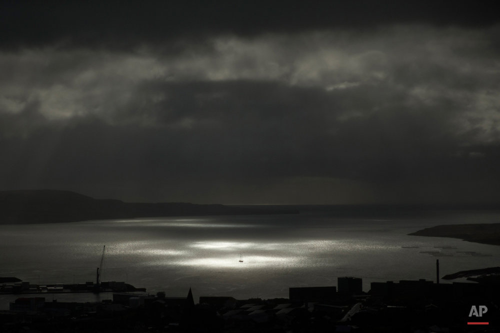 A spot of sunlight breaks through the clouds and shines on a vessel on the sea during the partial phase of a solar eclipse before totality as seen from a hill beside a hotel on the edge of the city overlooking Torshavn, the capital of the Faeroe Islands, Friday, March 20, 2015. A blanket of clouds in the Faeroe Islands blocked thousands of people there from experiencing the full effect of the total eclipse. The clouds then cleared after totality.  (AP Photo/Matt Dunham)