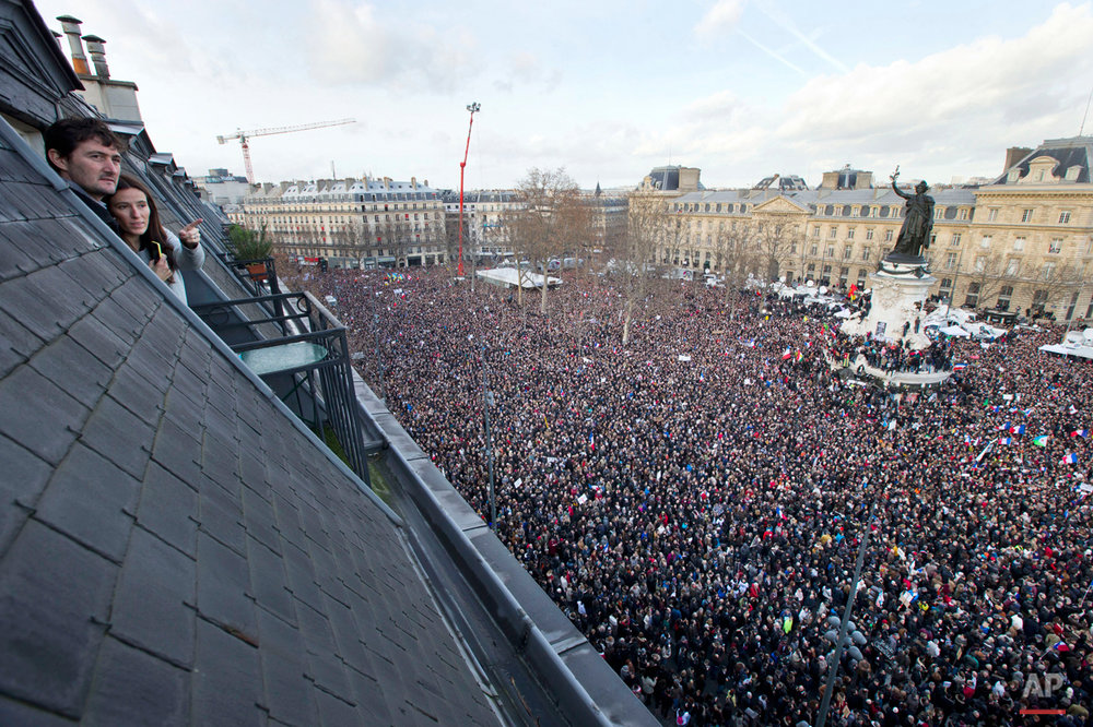 People watch from their roof-top apartment as some thousands of people gather at Republique square in Paris, France, Sunday, Jan. 11, 2015. Thousands of people began filling France's iconic Republique plaza, and world leaders converged on Paris in a rally of defiance and sorrow on Sunday to honor the 17 victims of three days of bloodshed that left France on alert for more violence. (AP Photo/Peter Dejong)