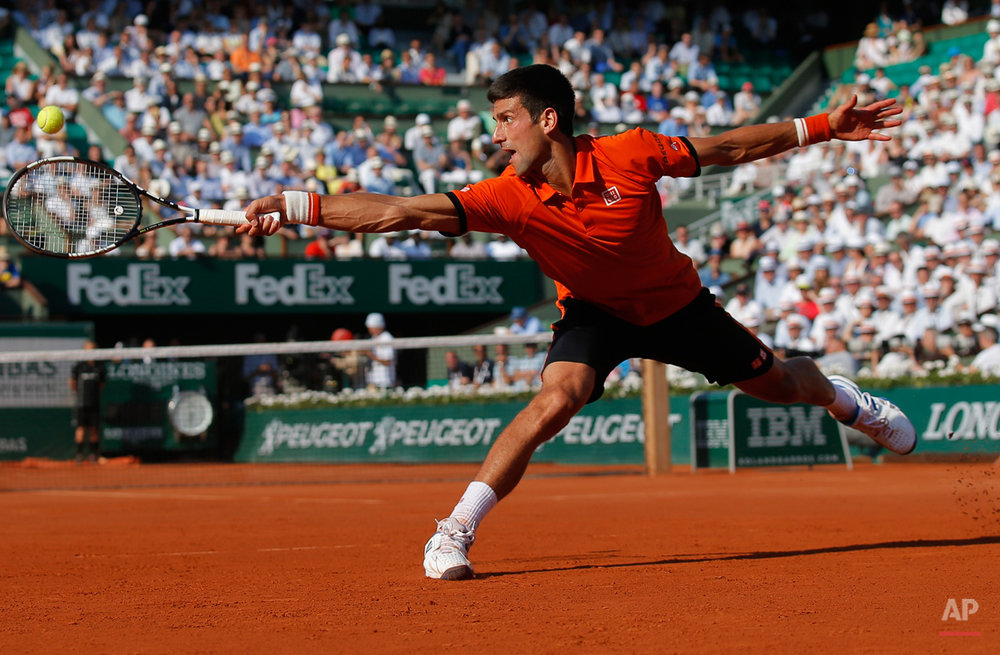 In this June 5, 2015 photo, Serbia's Novak Djokovic stretches to return the ball to Britain's Andy Murray, right, during their semifinal match of the French Open tennis tournament at the Roland Garros stadium in Paris, France. (AP Photo/Francois Mori)