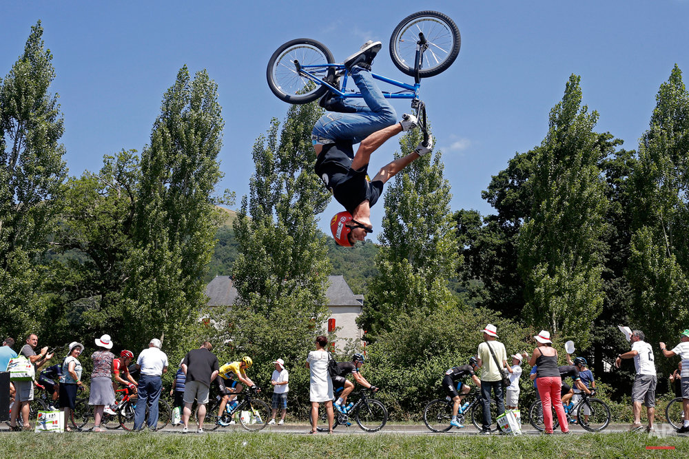 In this Tuesday, July 14, 2015 photo, a man performs a BMX bike stunt as the pack with Britain's Christopher Froome, wearing the overall leader's yellow jersey, passes during the tenth stage of the Tour de France cycling race over 167 kilometers (103.8 miles) with start in Tarbes and finish in La Pierre-Saint-Martin, France. (AP Photo/Laurent Cipriani)