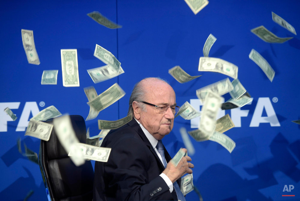 In this Wednesday, Aug. 5, 2015 photo, FIFA president Sepp  Blatter is photographed while banknotes thrown by British comedian Simon Brodkin hurtle through the air during a press conference following the extraordinary FIFA Executive Committee at the  headquarters in Zurich, Switzerland.  (Ennio Leanza/Keystone via AP)