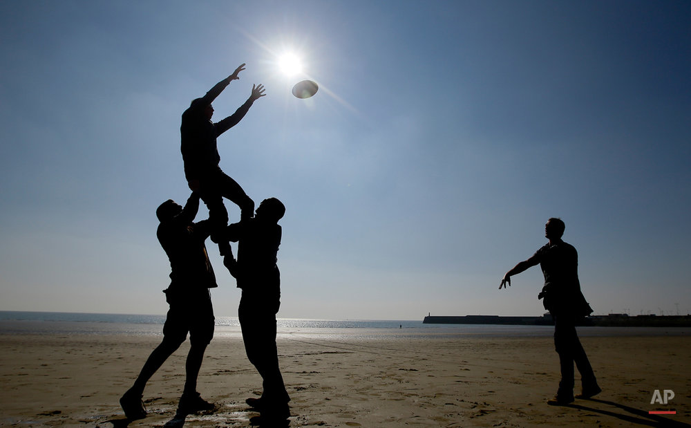 In this Oct. 2, 2015 photo, rugby fans are silhouetted as they play rugby on the beach at Porthcawl, a seaside town near Cardiff in Wales.  (AP Photo/Kirsty Wigglesworth)