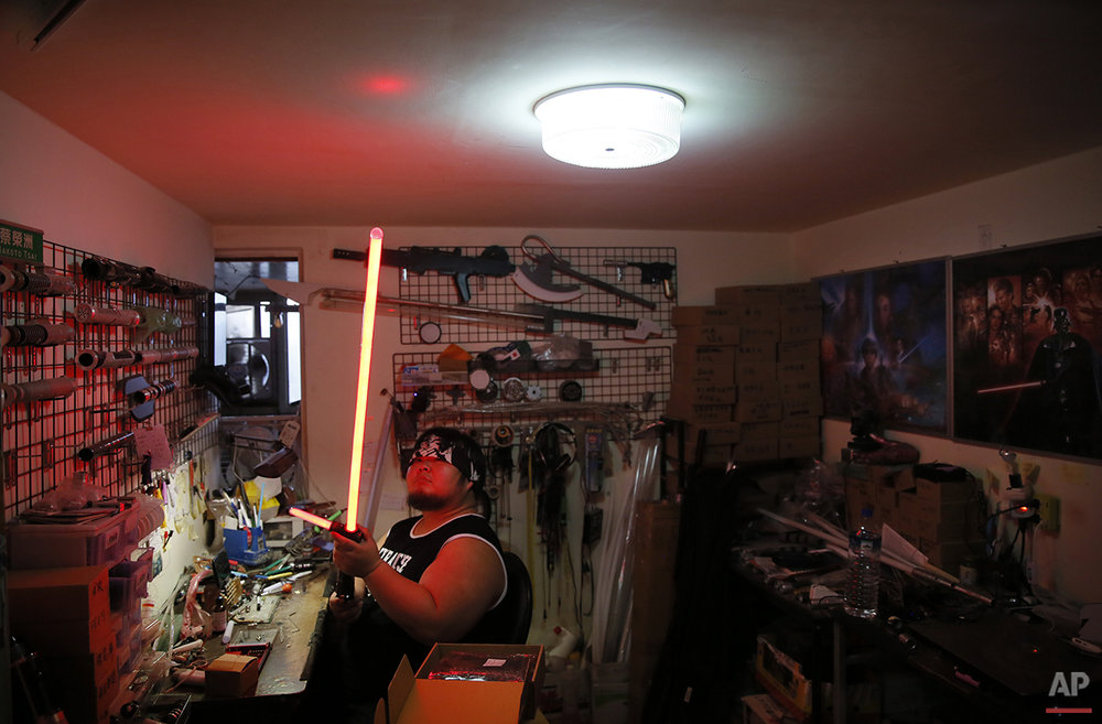 "In this photo made on Monday, Dec. 14, 2015, 32 year old Tsai Jung-chou or known by sci-fi fans as ""Makoto Tsai"", upgrades a replica Star Wars lightsaber with his personally designed LEDs and sound card at his home workshop in New Taipei City, Taiwan. A former optical engineer, Tsai now designs and fabricates his own versions of the iconic sci-fi weapon which he sells for up to $400 per model. (AP Photo/Wally Santana)"
