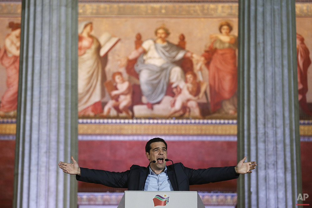 In this photo taken on Sunday, Jan. 25, 2015, leader of Syriza left-wing party Alexis Tsipras speaks to his supporters after his election victory outside Athens University Headquarters. Anyone hoping Greece might finally have a quiet year was quickly disappointed in 2015. Brinkmanship with bailout lenders brought the country a half-step from financial collapse and eurozone exit, while Greece was at the center of Europe's worst refugee crisis since World War II. (AP Photo/Petros Giannakouris)