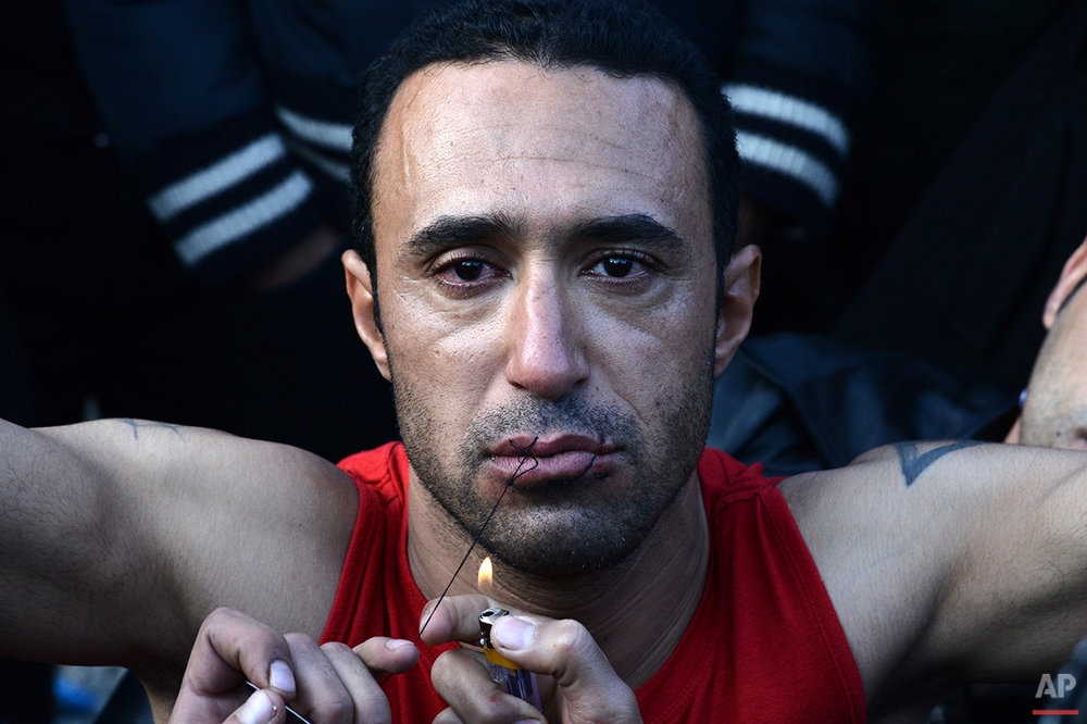 In this photo taken on Thursday, Nov. 26, 2015, an Iranian migrant has his mouth sewn shut during a protest near the village of Idomeni at the Greek-Macedonian border. Anyone hoping Greece might finally have a quiet year was quickly disappointed in 2015. Brinkmanship with bailout lenders brought the country a half-step from financial collapse and eurozone exit, while Greece was at the center of Europe's worst refugee crisis since World War II.  (AP Photo/Giannis Papanikos)
