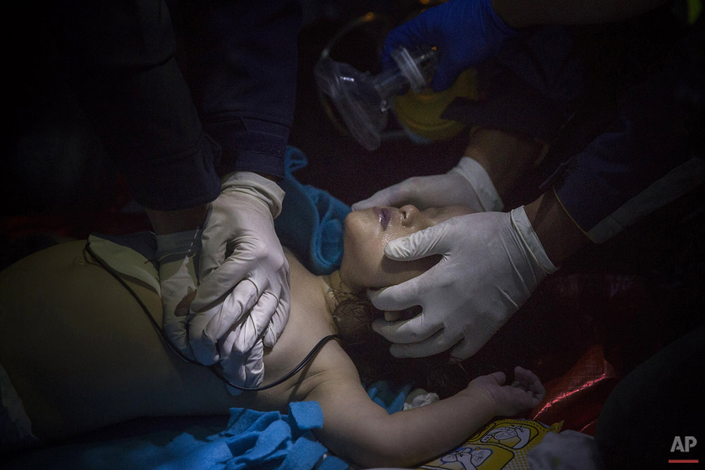 In this photo taken on Wednesday, Oct. 28, 2015, paramedics and doctors try to revive a baby after a boat with refugees and migrants sunk while was crossing the Aegean sea from Turkey to the Greek island of Lesbos. Anyone hoping Greece might finally have a quiet year was quickly disappointed in 2015. Brinkmanship with bailout lenders brought the country a half-step from financial collapse and eurozone exit, while Greece was at the center of Europe's worst refugee crisis since World War II. (AP Photo/Santi Palacios)