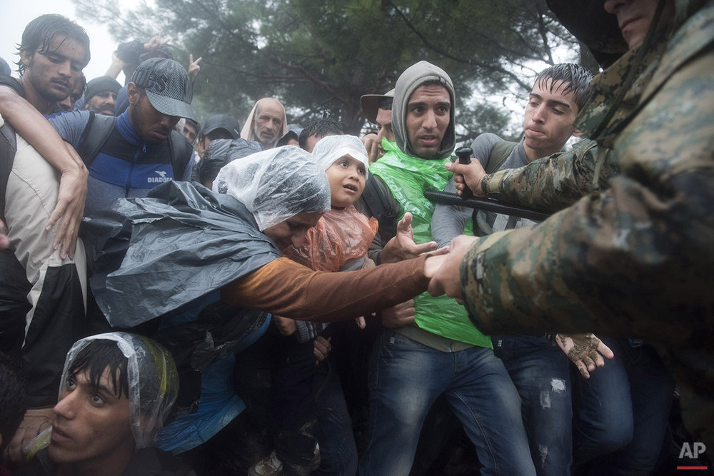 In this photo taken on Thursday, Sept. 10, 2015, Macedonian border police helps refugees and migrants to pass in heavy rainfall from the northern Greek village of Idomeni to southern Macedonia. Anyone hoping Greece might finally have a quiet year was quickly disappointed in 2015. Brinkmanship with bailout lenders brought the country a half-step from financial collapse and eurozone exit, while Greece was at the center of Europe's worst refugee crisis since World War II. (AP Photo/Giannis Papanikos)