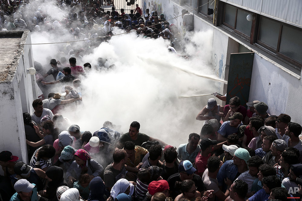 In this photo taken on Tuesday, Aug. 11, 2015, policemen try to disperse hundreds of migrants by spraying them with fire extinguishers, during a registration procedure which was taking place at the stadium of Kos town, on the southeastern island of Kos, Greece. Anyone hoping Greece might finally have a quiet year was quickly disappointed in 2015. Brinkmanship with bailout lenders brought the country a half-step from financial collapse and eurozone exit, while Greece was at the center of Europe's worst refugee crisis since World War II. (AP Photo/Yorgos Karahalis)