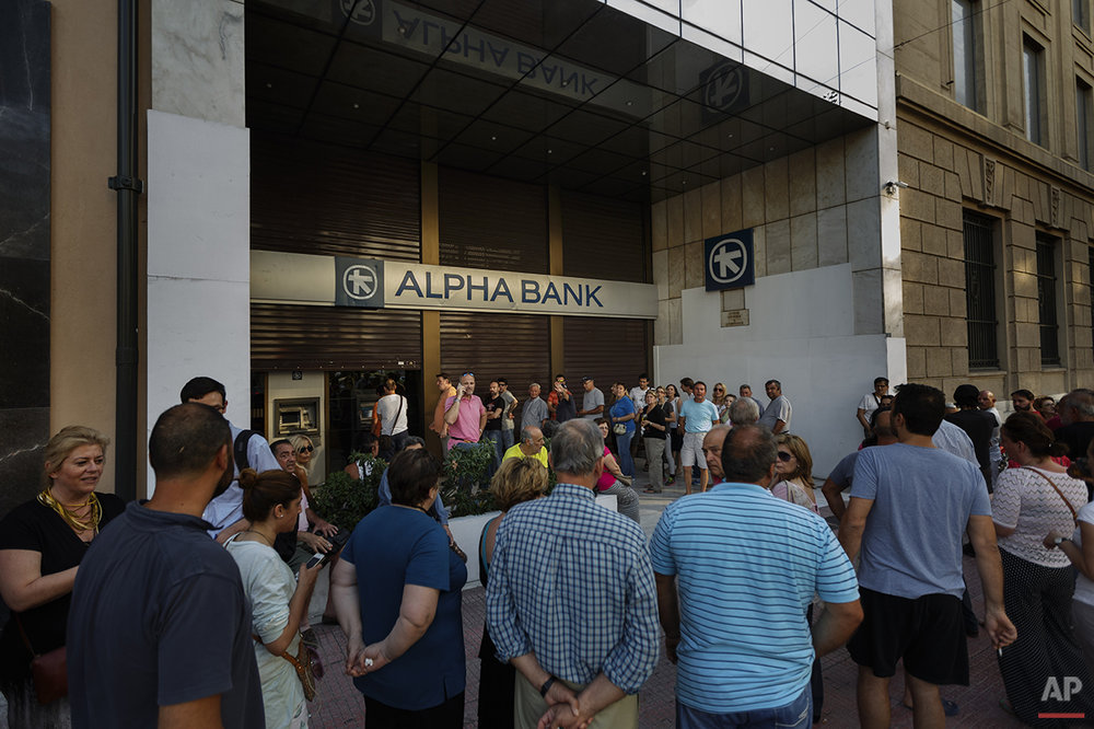 In this photo taken on Sunday, June 28, 2015, people stand in a queue to use an ATM cash machine of a bank in central Athens. Anyone hoping Greece might finally have a quiet year was quickly disappointed in 2015. Brinkmanship with bailout lenders brought the country a half-step from financial collapse and eurozone exit, while Greece was at the center of Europe's worst refugee crisis since World War II. (AP Photo/Daniel Ochoa de Olza)