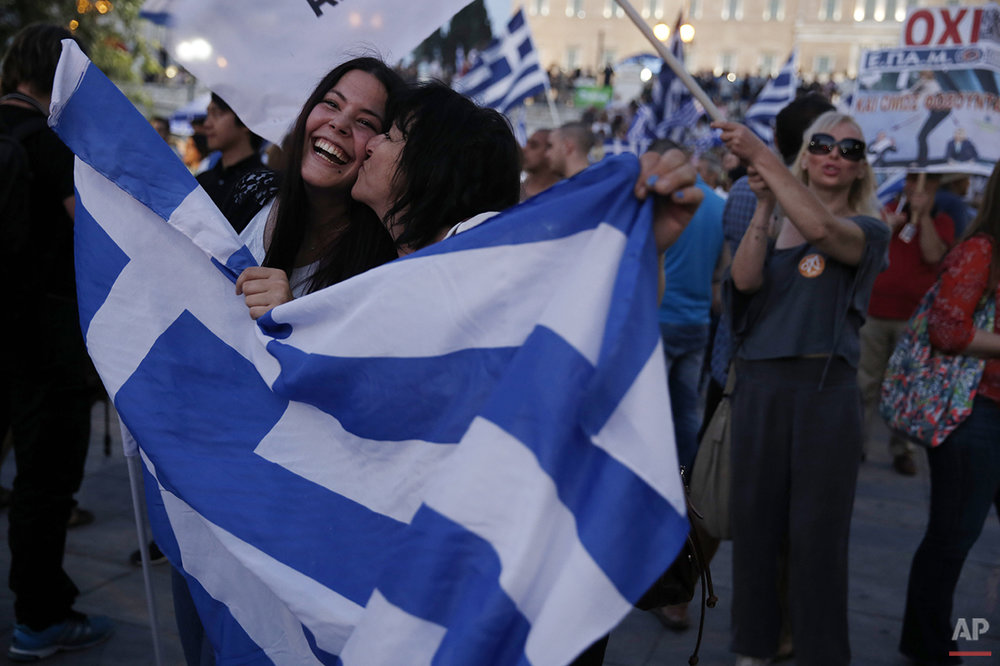 In this photo taken on Sunday, July 5, 2015, supporters of the No vote react after the results of the referendum at Syntagma square in Athens. Anyone hoping Greece might finally have a quiet year was quickly disappointed in 2015. Brinkmanship with bailout lenders brought the country a half-step from financial collapse and eurozone exit, while Greece was at the center of Europe's worst refugee crisis since World War II. (AP Photo/Petros Giannakouris)