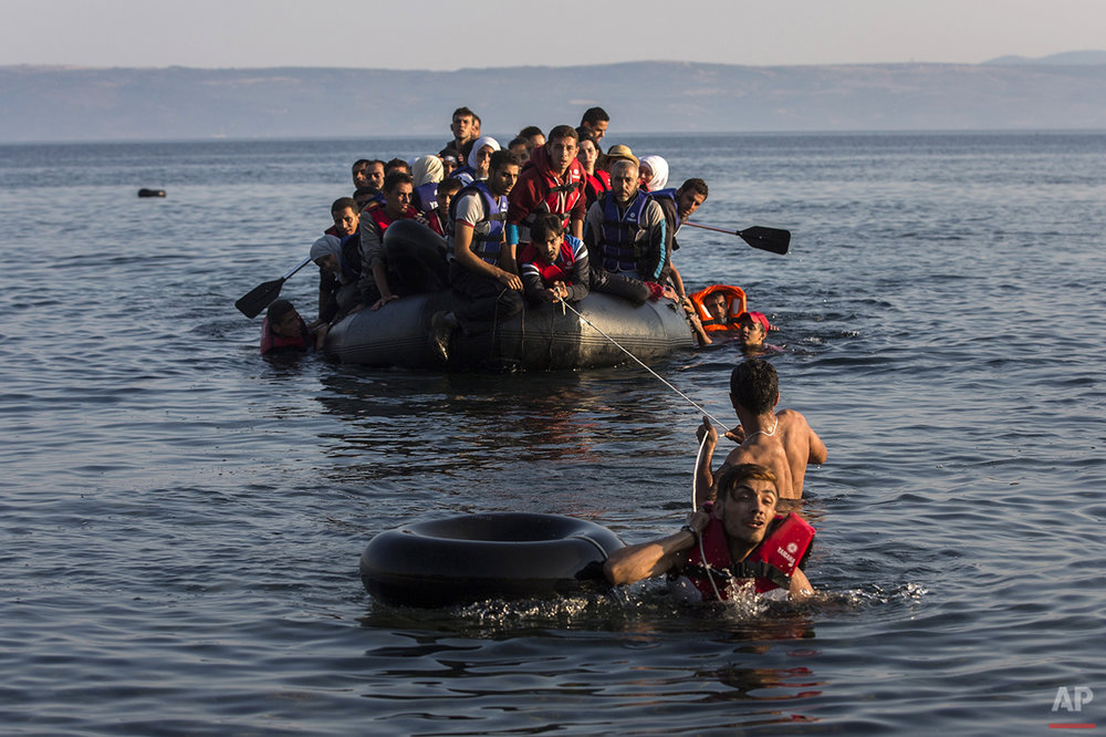 In this photo taken on Monday, July 27, 2015, two migrants pull an overcrowded dinghy with Syrian and Afghan refugees arriving from the Turkish coast to the Greek island of Lesbos. Anyone hoping Greece might finally have a quiet year was quickly disappointed in 2015. Brinkmanship with bailout lenders brought the country a half-step from financial collapse and eurozone exit, while Greece was at the center of Europe's worst refugee crisis since World War II.  (AP Photo/Santi Palacios)