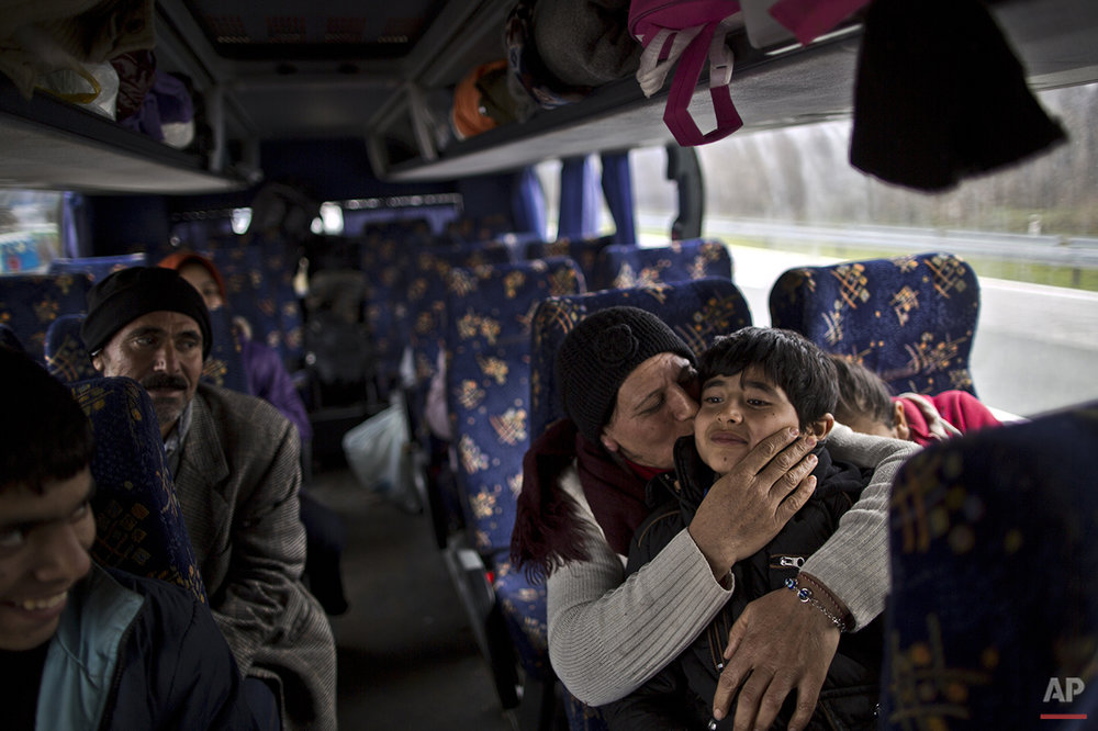 In this Sunday, Dec. 6, 2015 photo, Bessi Qasim, 42, a Yazidi refugee from Sinjar, Iraq, kisses her son Dildar, 10, as she and her family rest in a bus waiting to be transported to the train station in Sid where Serbian authorities load trains with refugees to Croatia, in Adasevci, Serbia. (AP Photo/Muhammed Muheisen)