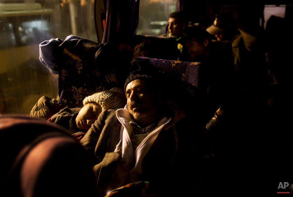 In this Sunday, Dec. 6, 2015 photo, Delphine Qasu, 18, a Yazidi refugee from Sinjar, Iraq, and her father Samir, 45, sleep in a bus while waiting with the rest of their family to be transported to the train station in Sid where Serbian authorities load trains with refugees to Croatia, in Adasevci, Serbia. The Qasus slept chiefly on trains, buses and benches while passing through registration centers in four Balkan countries (AP Photo/Muhammed Muheisen)