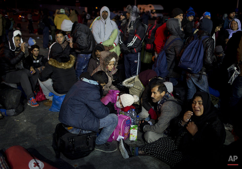 In this Thursday, Dec. 3, 2015 photo, Yazidi refugee Dunia Qasu, 13, from Sinjar, Iraq, sleeps surrounded by her family as they wait at the port of Mitylene on the northeast Greek island of Lesbos, waiting until midnight to get onboard a ferry traveling to Athens. (AP Photo/Muhammed Muheisen)