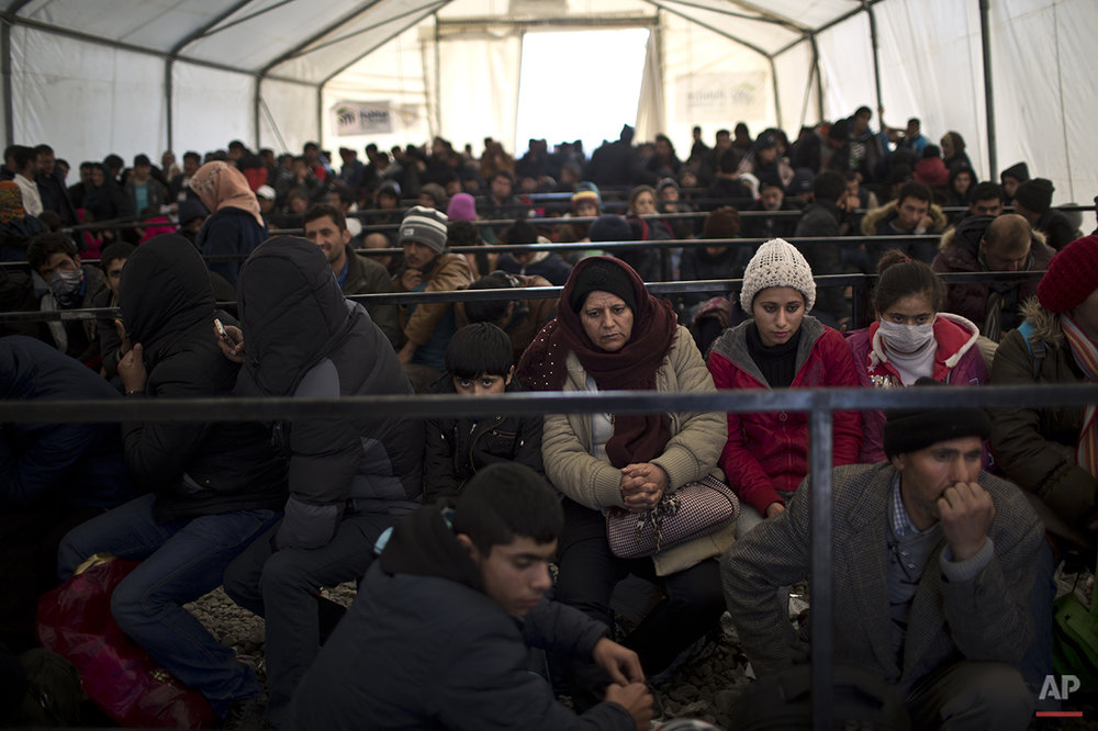 In this Saturday, Dec. 5, 2015 photo, Qasu family, a Yazidi refugee family from Sinjar, Iraq, wait at a registration camp near the southern Macedonian town of Gevgelija to board a train heading to the Serbian border. (AP Photo/Muhammed Muheisen)