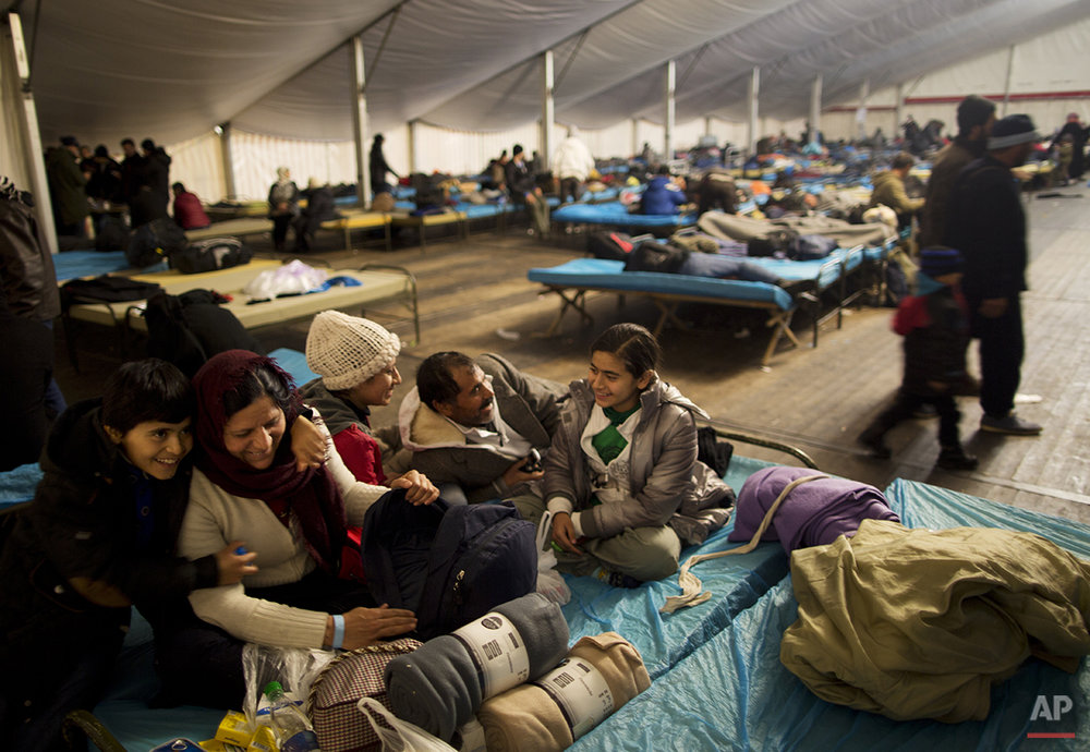 In this late Monday, Dec. 7, 2015 photo, the Qasu family, a Yazidi refugee family from Sinjar, Iraq, laugh with each other while resting on a bed in a shelter in Salzburg, Austria.  (AP Photo/Muhammed Muheisen)