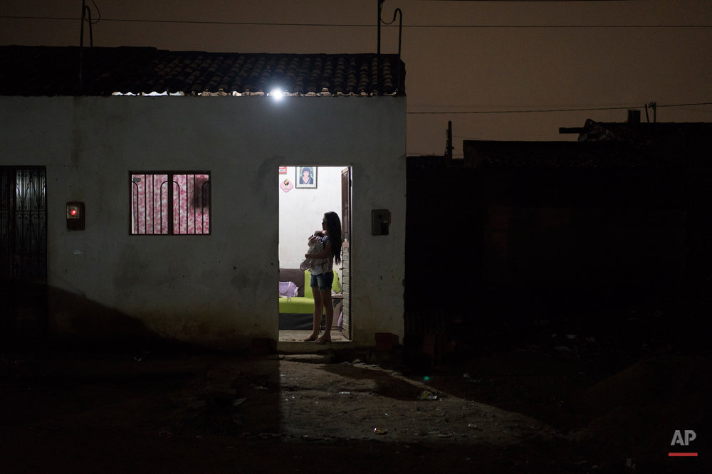 In this Dec. 22, 2015 photo, Angelica Pereira holds her daughter Luiza as she waits for her husband at their house in Santa Cruz do Capibaribe, Pernambuco state, Brazil. In the early weeks of Angelica Pereiraís pregnancy, a mosquito bite began bothering her. At first it seemed a small thing. But the next day she awoke with a rash all over her body, a headache, a fever and a burning in her eyes. The symptoms disappeared within four days, but she fears the virus has left lasting consequences. (AP Photo/Felipe Dana)