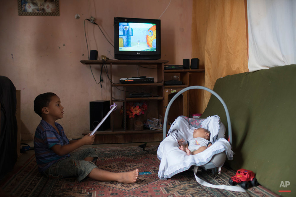 In this Dec. 23, 2015 photo, 5-year-old Elenilson, left, holds a notebook as he plays next to his 2-month-old brother Jose Wesley at their house in Poco Fundo, Pernambuco state, Brazil. Their mother, Solange Ferreira had never heard of microcephaly before her youngest son was diagnosed a couple of days after his birth. (AP Photo/Felipe Dana)