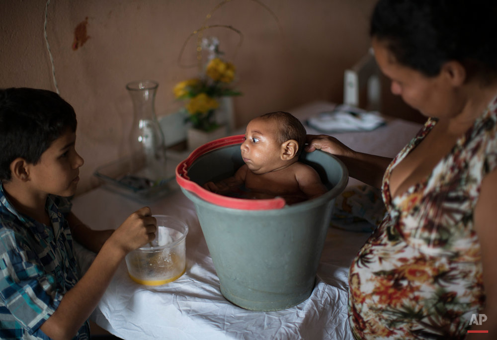 In this Dec. 23, 2015 photo, 10-year-old Elison, left, watches as his mother Solange Ferreira bathes Jose Wesley in a bucket at their house in Poco Fundo, Pernambuco state, Brazil. Ferreira says Jose Wesley enjoys being in the water, she places him in the bucket several times a day to calm him. (AP Photo/Felipe Dana)
