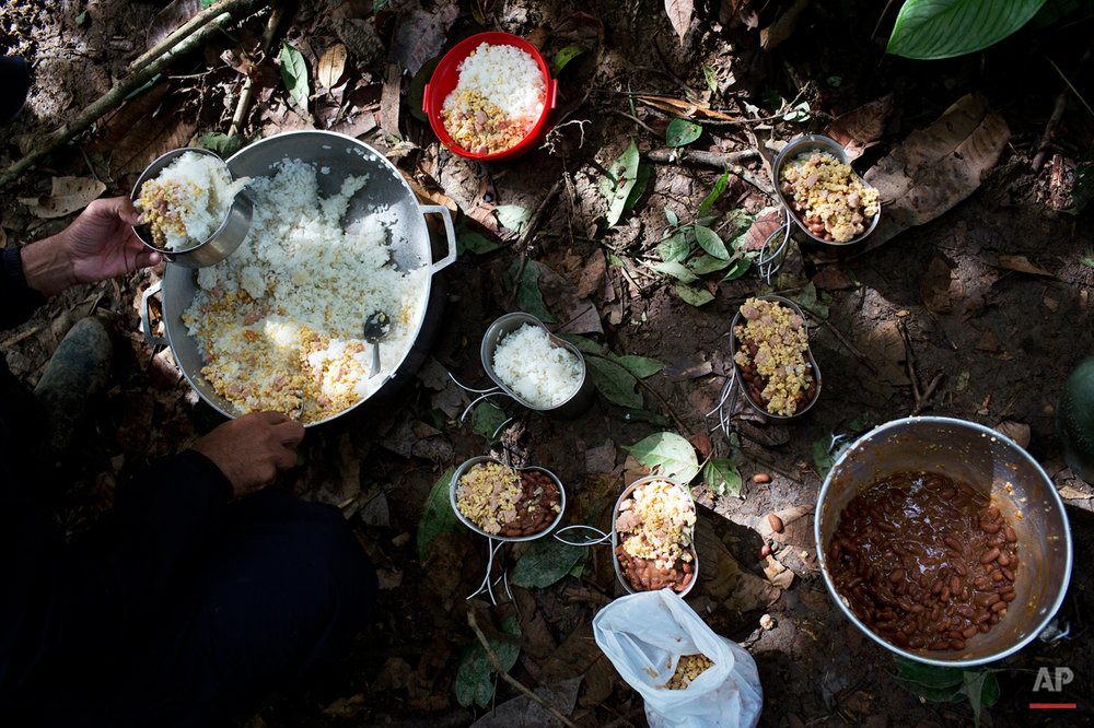 In this Jan. 4, 2016 photo, a rebel soldier of the 36th Front of the Revolutionary Armed Forces of Colombia, or FARC, serves up a portion of rice, eggs, sausage and beans, for breakfast, at a hidden camp in Antioquia state, in the northwest Andes of Colombia. If the FARC seems at times stuck in a time warp, rebels share an enormous gratitude to the insurgency for rescuing them from poverty, providing them with a ìfamilyî and sense of belonging. (AP Photo/Rodrigo Abd)
