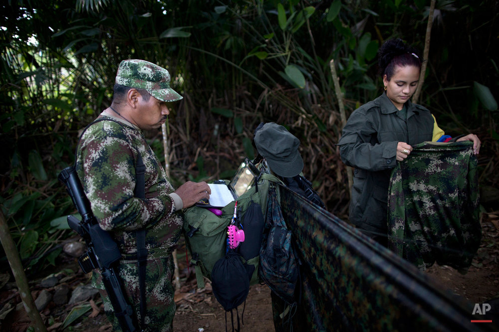 "In this Jan. 6, 2016 photo, Juan Pablo, a commander of the 36th Front of the Revolutionary Armed Forces of Colombia, or FARC,  works on his laptop, next to his girlfriend, 25-year-old rebel fighter Tania, at a hidden camp in Antioquia state, in the northwest Andes of Colombia. Tania says, ""If we sign the peace accords with the government, I would like to have two kids with Juan Pablo, study odontology and serve to the poor with my work."" (AP Photo/Rodrigo Abd)"