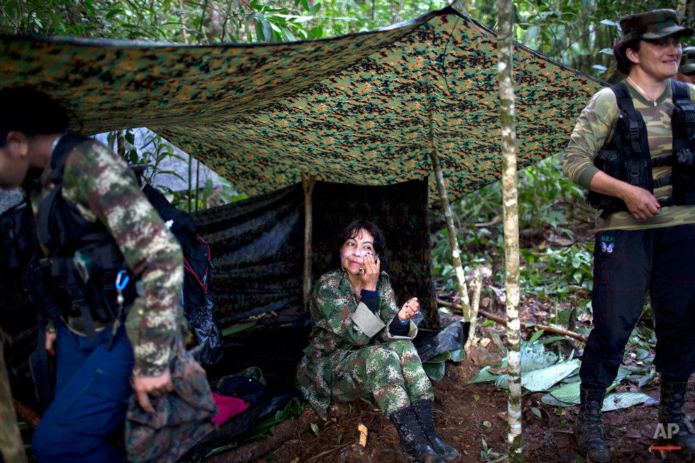 In this Jan. 4, 2016 photo, Yira Castro, a mid-level commander for the 36th Front of the Revolutionary Armed Forces of Colombia or FARC, rubs moisturizing creme on her face, in a hidden camp in Antioquia state, in the northwest Andes of Colombia. Castro is a sort-of den mother to other female rebels who in the FARC have found a sense of empowerment they say is lacking in macho Colombian society. (AP Photo/Rodrigo Abd)