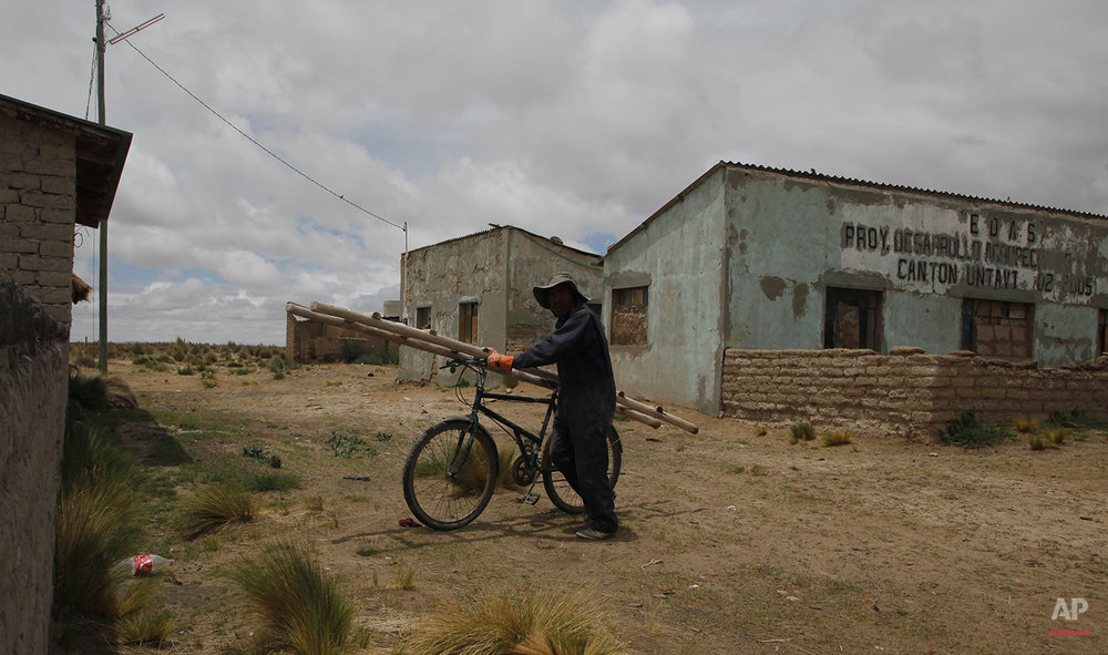 "In this Jan. 12, 2016 photo, fisherman Cirilo Choque, carries a ladder on his bicycle, as he walks to his job as bricklayer in Untavi, near the shores of Lake Poopo, Bolivia.  ""We are really worried because the lake dried up and that the authorities have not helped. Hopefully they will really help us. Before the lake dried up there were about 200 families living here, now only about 70 are left. Most are elderly people or children, the others left to find jobs in the city or other places."" said Choque. (AP Photo/Juan Karita)"