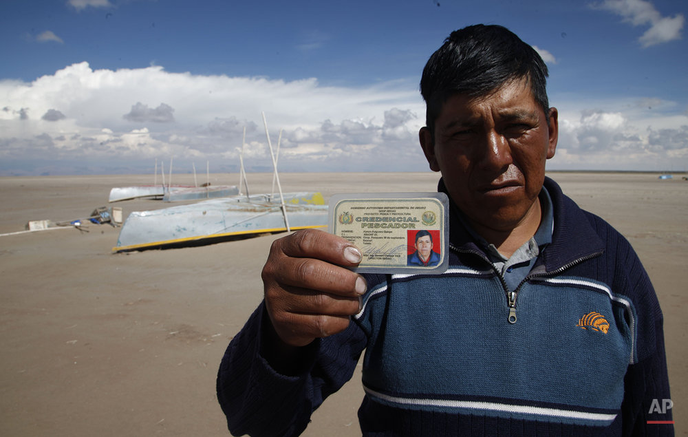 "In this Jan. 12, 2016 photo, Abraham Fulguera shows his fisherman's credential, in the dried up Lake Poopo, on the outskirts of Untavi, Bolivia. ""I am the president of the September 10 Fishing Cooperative. We used to be 30 fishermen and there used to be ten or more fishing cooperatives in Lake Poopo. Now we work as construction laborers. Others have left to look for jobs. I hope we do not become a ghost town. We have faith that the lake will come back."" Fulguera said. (AP Photo/Juan Karita)"