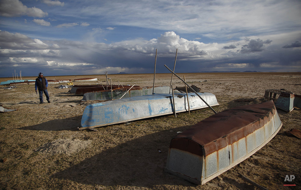 In this Jan. 11, 2016 photo, a fisherman walks along the abandoned boats in the dried up Lake Poopo, on the outskirts of Untavi, Bolivia. The overturned fishing skiffs lie abandoned on the dried up former shores of what was Bolivia's second-largest lake. (AP Photo/Juan Karita)