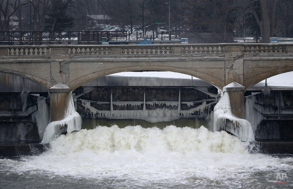 Water from the Flint River flows through the Hamilton Dam near downtown Flint, Mich., on Jan. 21, 2016. As a part of efforts to get the city's finances in line, its water source was changed in April 2014, from a supply treated in Detroit and piped to Flint, to Flint River water treated and disseminated locally. It wasn't long before residents began complaining of yellow and brown water from their taps, along with an unpleasant taste and smell. People began seeing rashes on their skin and clumps of hair falling from their heads. Workers at a remaining GM plant found their parts were corroding. (AP Photo/Paul Sancya)