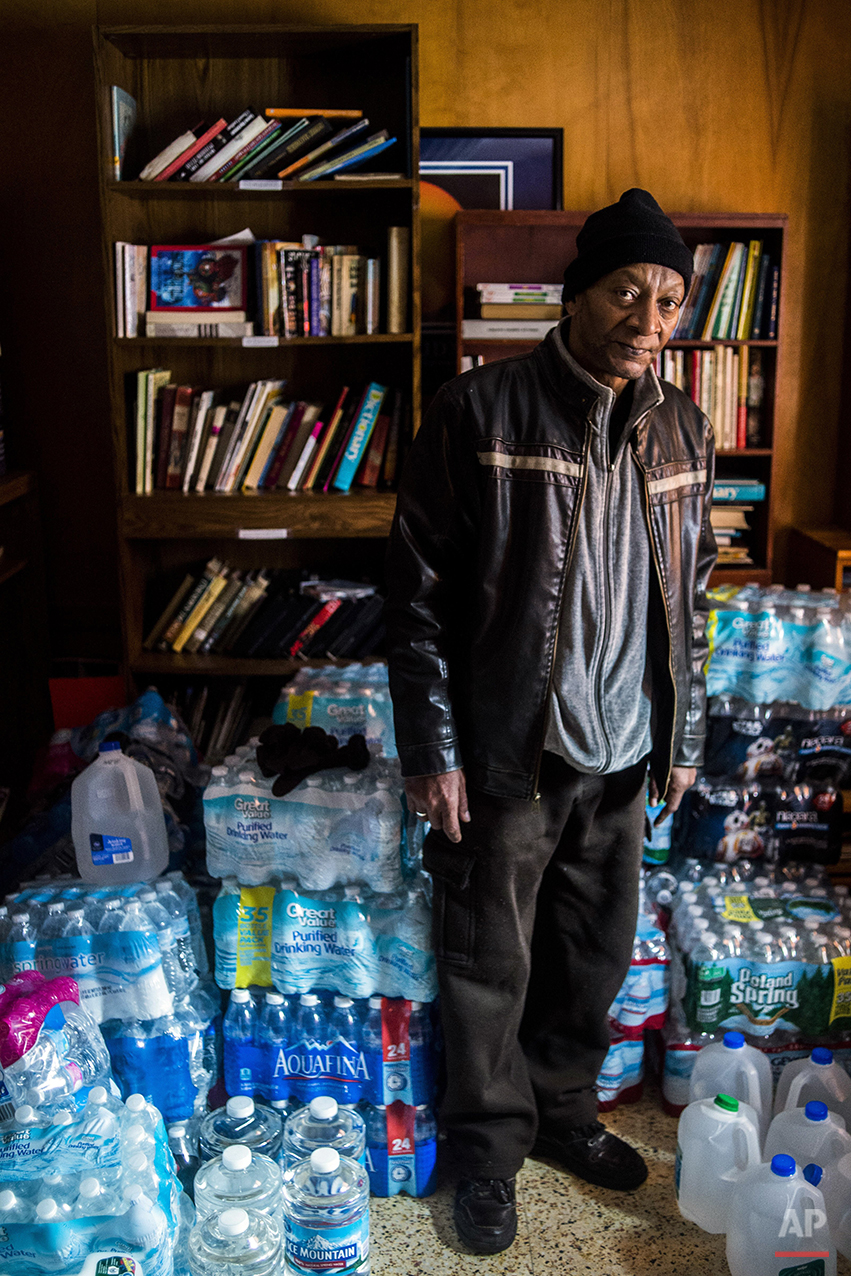 "Flint, Mich., resident Michael Simmons, 61, stands amongst gallons and cases of bottled water as he arrives to pick up free water from Pastor Bobby Jackson after Detroit-area volunteers dropped off more than 500 cases of bottled water in Flint on Saturday, Jan. 16, 2016, coordinating with Mission of Hope on Flint's north side. ""It's a disgrace. It's shameful. I can't believe it,"" Simmons said. ""That the governor of Michigan would know about what has been done to Flint and not do anything about it? He needs to be locked up."" (Jake May/The Flint Journal-MLive.com via AP)