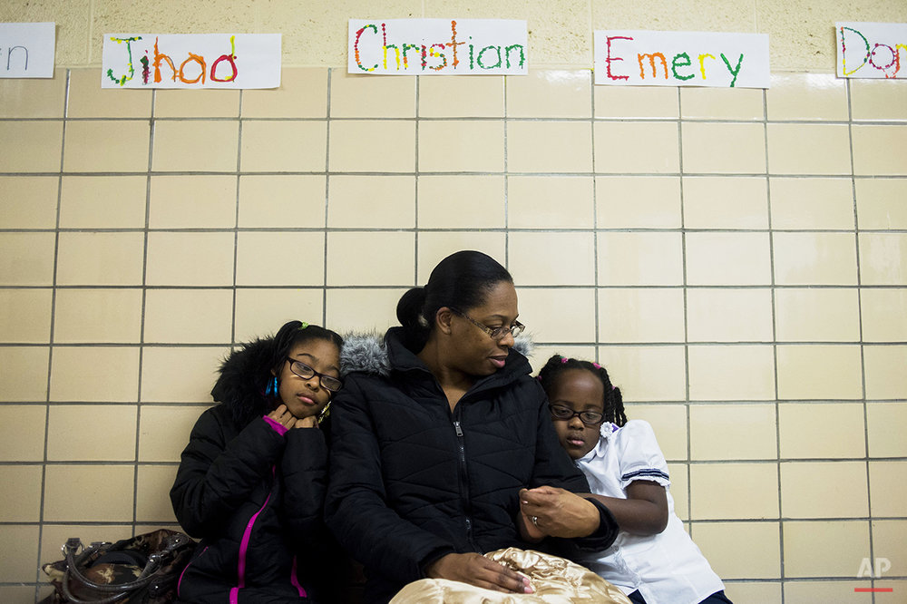 LaShanti Redmond, 10, left, and her sister Asharra Smith, 6, hold onto their mother Charlene Mitchell, all of Flint, for comfort as they wait to get their blood tested for lead levels in Flint, Mich., Tuesday, Jan. 12, 2016. The Flint Community Schools, the Genesee County Health Department and Molina Healthcare held a family fun night at the school to get children ages 0 to 6-year-olds tested for lead levels in their blood. The next testing event will be held at Eisenhower Elementary on Jan. 26. (Jake May/The Flint Journal-MLive.com via AP) 